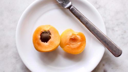 Спелый абрикос, разрезанный пополам