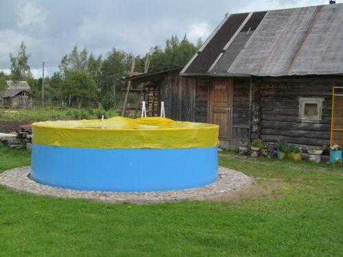 Бассейн, накрытый чехлом, во дворе дома