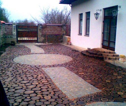 Площадка перед домом, оформленная спилами деревьев