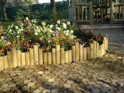 Площадка у садовой клумбы, оформленная срезами деревьев