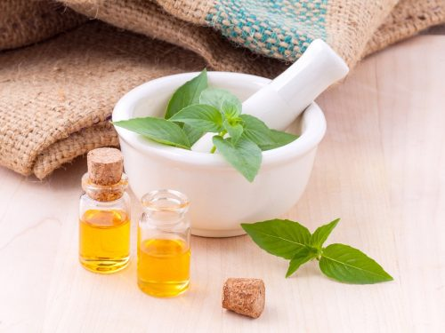 Эфирные масла, зелень мяты, ступка и пестик
